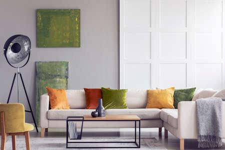 Gelbe und grüne Kissen auf weißem Sofa im Wohnzimmerinnenraum mit Gemälden und Lampe. Echtes Foto Standard-Bild