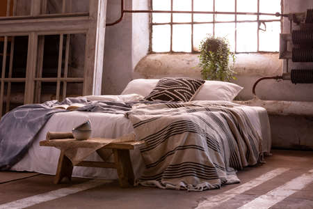 Double bed with pillows and blanket, wooden stool and plant in a wabi sabi bedroom interior Stock Photo - 109518690