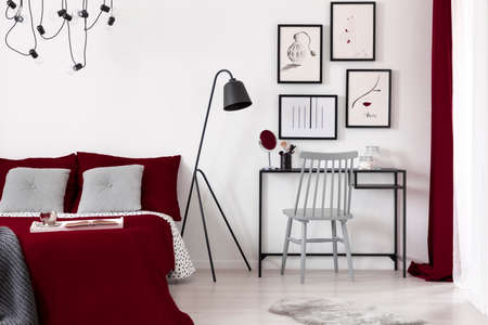 A gallery of illustrations on a white wall above a small desk which is next to a black metal lamp and a burgundy bed in a modern bedroom interior. Real photo.