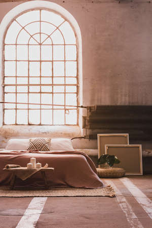 Arch window in a wabi sabi bedroom interior with a bed and iron radiator. Real photo
