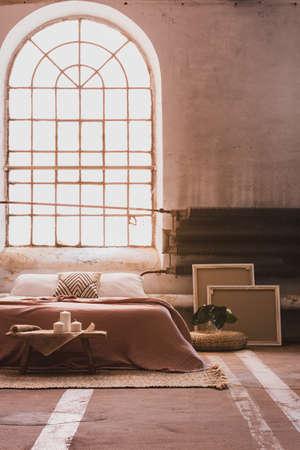 Ventana de arco en el interior de un dormitorio wabi sabi con cama y radiador de hierro. Foto real Foto de archivo