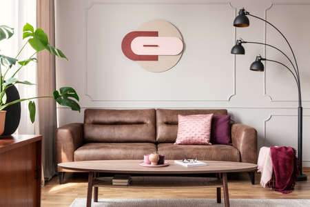 Lamp next to leather settee in modern apartment interior with plant, table and poster. Real photo