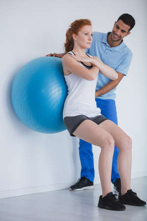 Female client working out with a ball during a training with a personal trainer Banque d'images - 109518667