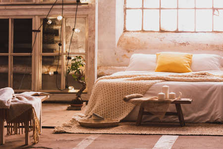 Cozy bedroom interior with a bed, stool, candles and industrial window. Real photo