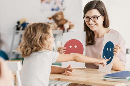 Emotionsemoticons, die von einem Psychologen während einer Therapiesitzung mit einem Kind mit einer Autismus-Spektrum-Störung verwendet werden.