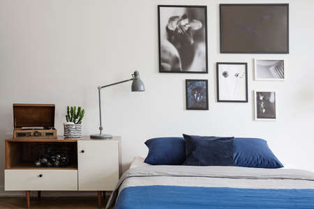 Scandinavian style, wooden dresser by a navy blue bed and framed art gallery on a white wall of a creative bedroom interior Stock Photo