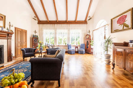 A view of a luxurious high ceiling living room interior with wooden floor, sunny windows and classic settee, armchairs and cabinet. Empty space on the floor. Real photo. Stock Photo