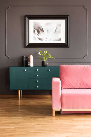 Poster above green cupboard in grey loft interior with pink couch on wooden floor. Real photo Stock Photo
