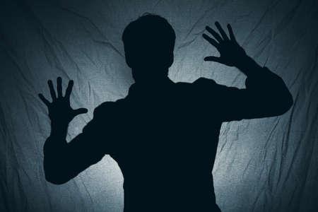Ombra di un uomo dietro un tessuto scuro Archivio Fotografico