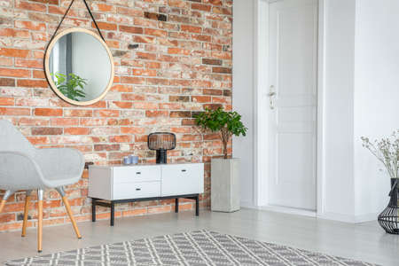 Mirror on red brick wall above white cupboard and grey armchair in living room interior. Real photo Stock fotó - 109842512