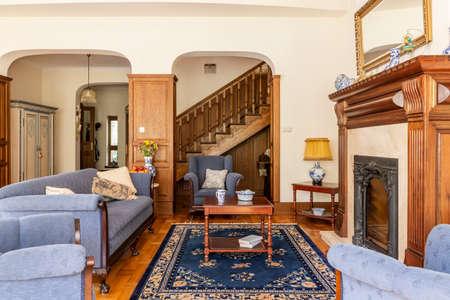 Interior de una lujosa sala de estar con sofá antiguo y mesa de café frente a una chimenea en una mansión de estilo inglés. Escalera de madera al fondo. Foto real. Foto de archivo