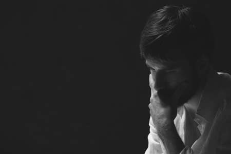 Black and white portrait of handsome worried man, photo with copy space on dark background Stock Photo - 109575388