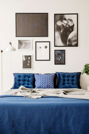 Mock-up picture gallery on a white wall above a large bed with navy blue bedding in a bright and modern bedroom interior Stock Photo