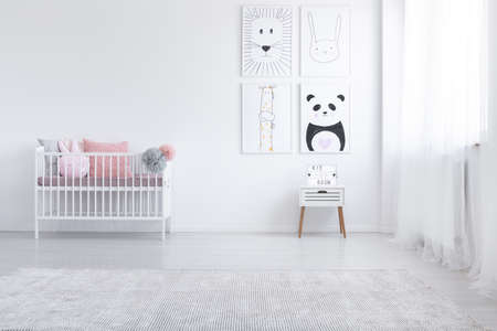 Pink pillow in cradle and posters on the wall in white child's room interior with carpet. Real photo Archivio Fotografico