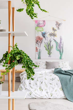 Close to nature bright bedroom interior with a bed covered with white linen and marine blanket. Green plants on shelves next to the bed. Fabric art wall. Real photo.