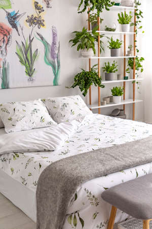 White and green organic linen and gray wool blanket on a bed in a bright bedroom interior full of plants. Real photo. Stock fotó