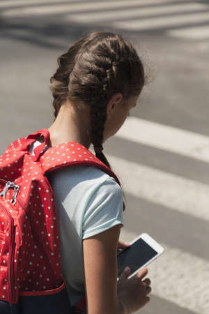 Girl with backpack and smartphone walking on pedestrian crossing