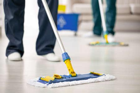 Primer plano de un trapeador en el suelo sostenido por un experto en limpieza mientras se purifica el interior Foto de archivo