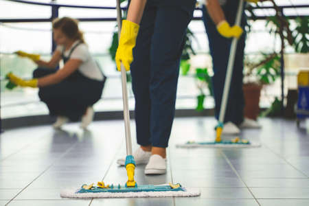 Close-up on professional cleaner with yellow gloves and mop wiping the floor 스톡 콘텐츠 - 109806878