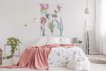 Peach blanket and white with green pattern linen on bed in a natural bright bedroom interior. Tapestry with colorful flowers and birds on the back wall. Real photo.