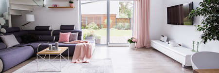 Panorama of modern living room interior with window between corner sofa and television. Real photo