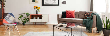 Horizontal photo of a living room interior with a sofa, table, sunflowers and patterned chair. Real photo Stock Photo