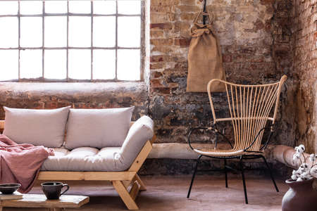 Armchair next to grey sofa with cushions in industrial interior with window and red brick wall. Real photo