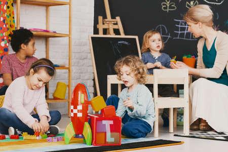Multiculturele kinderen spelen samen in de kleuterschool met een groot bord