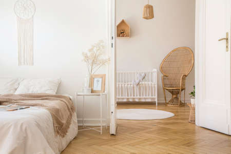 Blanket on white bed in bedroom interior with peacock chair next to child's cradle. Real photo Standard-Bild