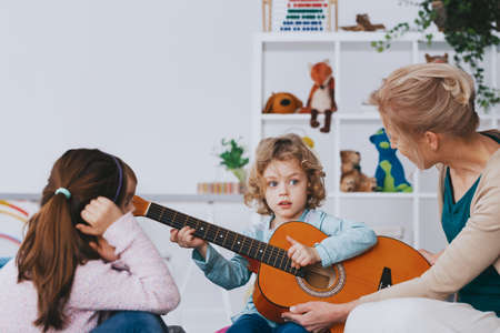Cute little boy learning how to play guitar during lesson in preschool, photo with copy space