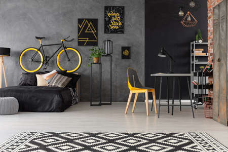 Patterned carpet and chair at desk in grey room interior with posters and bike above bed. Real photo
