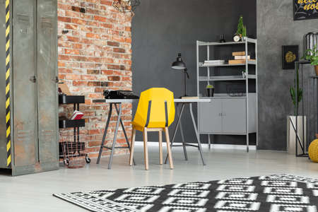 Yellow chair at desk in teenagers room interior with metal cabinet against red brick wall. Real photo