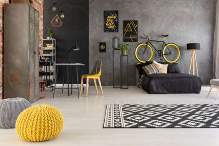 Yellow pouf and patterned carpet in grey teenagers room with bike above black bed. Real photo