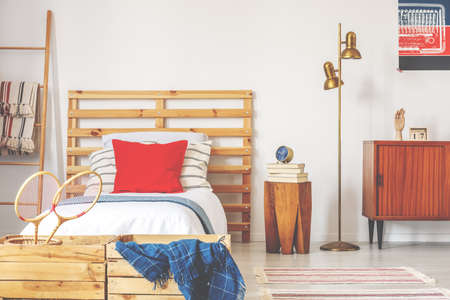 Stylish teenager bedroom interior with wooden bed and vintage furniture, real photo Stock Photo