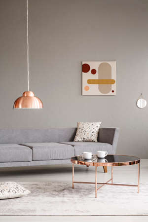 Cups on a shiny, copper golden coffee table in a minimalist living room interior with a large gray sofa Stock Photo