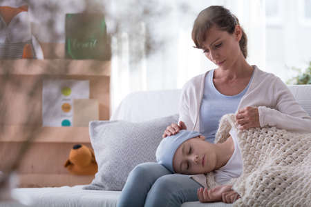 Worried mother and daughter with cancer taking rest at home