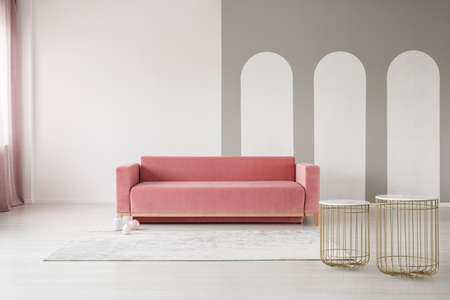 Golden basket tables and a pink velvet sofa in an elegant living room interior with gray arches on a white wall