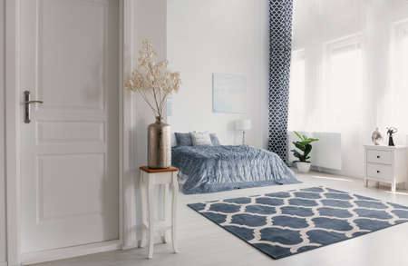 Flower in silver vase on the wooden table next to closed door to elegant new york style bedroom with patterned carpet and white furniture, real photo 스톡 콘텐츠