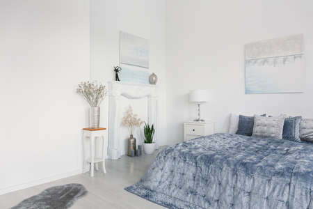 Big comfortable bed with elegant blue bedding, white fireplace portal and flowers in silver vases, real photo with copy space