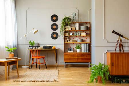 Vinyl-Schallplatten-Dekorationen an einer grauen Wand mit Formteilen und Holzmöbeln in einem Retro-Home-Office-Interieur für einen Schriftsteller. Echtes Foto. Standard-Bild