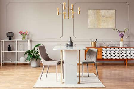 Lámpara colgante dorada de estilo industrial sobre una mesa de mármol excepcional en el interior de un comedor moderno con una decoración ecléctica Foto de archivo
