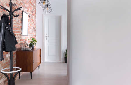 Stylish apartment hall clothes hanger, cupboard and brick wall, real photo with copy space