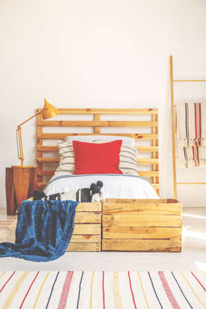 Vertical view of comfortable bed with wooden headboard, red pillow and bright bedding, bedroom interior with copy space on the white wall