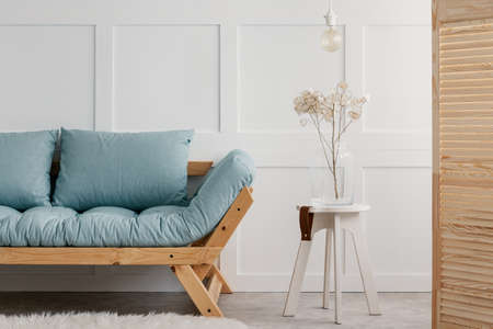Plant and lamp on white stool next to blue wooden sofa in minimal living room interior. Real photo