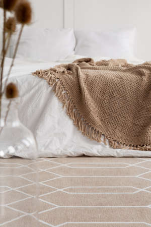 Patterned carpet in natural bedroom interior with brown blanket on white bed. Real photo Stok Fotoğraf