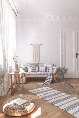 Sunbeams on a wicker ottoman and herringbone floor of a beige living room interior with a wooden sofa and cushions