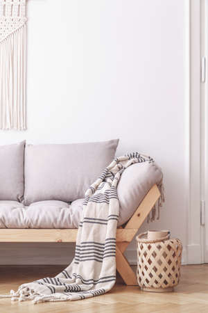 Plywood lantern next to a wooden sofa with gray cushions and a blanket in a simple living room interior