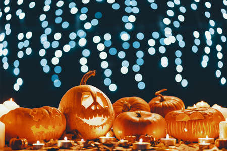 Table with autumn leaves, candles and carved pumpkins in real photo with lights in blurred background