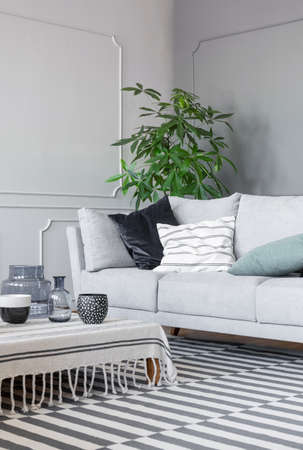 Patterned rug and coffee table with mugs and glass vases in the stylish living room with grey sofa