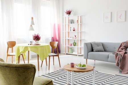 Patterned carpet on the floor of stylish living room with grey couch, round table and chairs and heather paintings on the wall, real photo Stock Photo